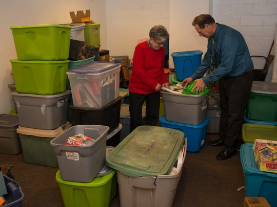 Shop Manager Ilene Miller and Jeff Potter look through some of containers of items he donated.