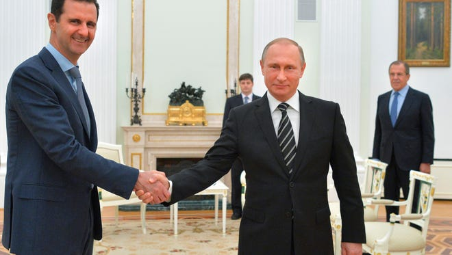 Russian President Vladimir Putin, center, shakes hand with Syrian President Bashar Assad as Russian Foreign Minister Sergey Lavrov, right, looks on in the Kremlin in Moscow, Russia, on Oct. 20.