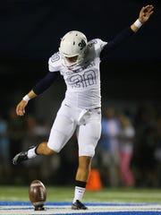 Naples High School's Jerry Nunez kicks off against