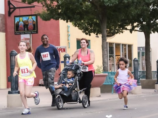 Participants in the Electric 5K Road Race, hosted by the Las Cruces Running Club, run the 3.1 mile course downtown in July 2014.