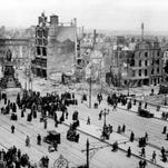 Parts of Dublin are in ruins after the Easter Rising on April 24, 1916.  At right is the O'Connell Bridge continuing into O'Connell Street with the O'Connell monument, at left, and the ruined area around the Eden Quay.
