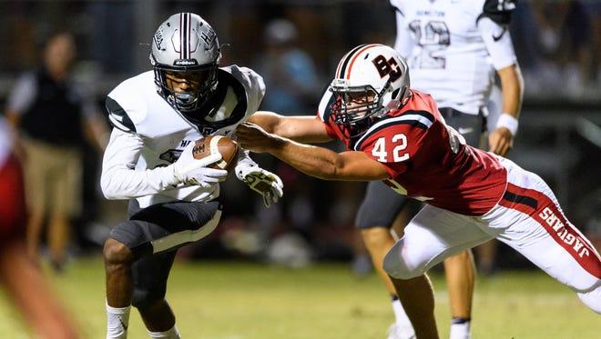 Hamilton's Jawhar Jordan Jr. (#25) rushes against Boulder Creek's Hunter Jaskey (#42) for a 7-yard touchdown in the second quarter of their high school football game on Friday, Aug. 18, 2017, at Boulder Creek High School in Anthem, Ariz.
