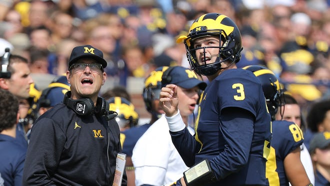 Michigan coach Jim Harbaugh and quarterback Wilton Speight watch the video replay in the first quarter against Air Force at Michigan Stadium on Sept. 16, 2017.