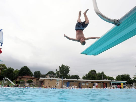 Chris Johrendt, 15, does a front flip off the diving board at Buchner Pool in this file photo. The city is considering renovating the pool, which is standing on its last legs, and the talks have spurred a lot of input from residents.