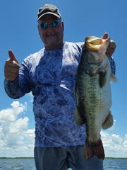 Capt. JoGene Holaway holds up his FWC trophy catch largemouth black bass that he caught while fishing with Steve Dial on Lake Trafford.  Holaway caught this bass on a black bluejig with a brusier bait crazy craw. The fish was released after the photo.