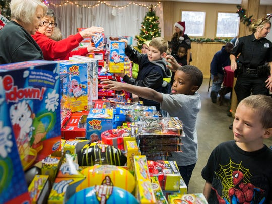 Kids line up to pick out presents from the large selection of games and toys  at the annual Evansville FOP Christmas party on Saturday morning.