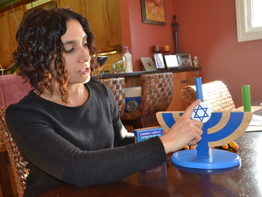 Shari Corona uses her children's toy menorah to explain the proper way to light one.
