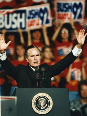 President George Bush waves from the podium at Austin Peay State University on his Tennessee campaign stop in Clarksville Sept. 29, 1992.