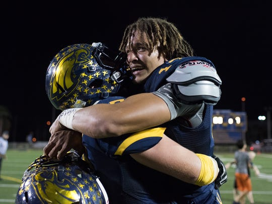 Naples quarterback Jordan Persad-Tirone cries in celebration with teammate Matt Myers after Naples pulled out a last-second win over Port Charlotte at Naples High on Friday night.