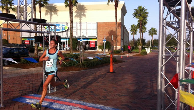 Sarah Simonetti finishes first in the World of Beer Tap It and Run 5K at the Avenue Viera.