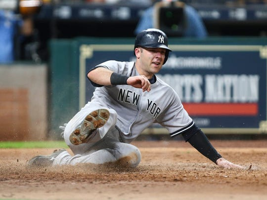 New York Yankees catcher Austin Romine (27) slides home to score a run during the sixth inning against the Houston Astros at Minute Maid Park on Friday, June 30, 2017.