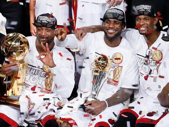 Chris Bosh, right, celebrates winning an NBA title with teammates.