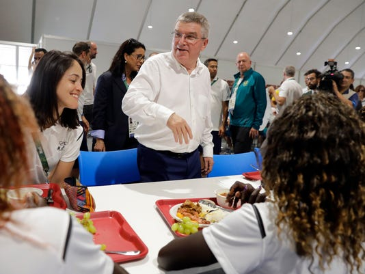 International Olympic Committee President Thomas Bach, center, sits down to chat with members of the Refugee Olympic Team as they eat lunch in the athletes village in advance of the 2016 Olympic Games in Rio de Janeiro, Brazil, Monday, Aug. 1, 2016. (AP Photo/Patrick Semansky, Pool)