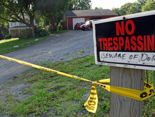 Police tape remains on the property on Monday, June