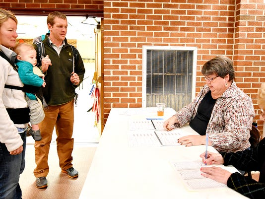 )From left, Lauralee Trump, with Henry Trump, 8-months-old, and her husband Mike Trump, with two-year-old Gwen Trump, wait for their names to be found on the list of registrants by Majority Inspector Zina Compton and Clerk Gloria Gross-Boisvert, at Aldersgate U.M. Church in York Township during election night in York, Pa. on Tuesday, Nov. 3, 2015. Dawn J. Sagert - dsagert@yorkdispatch.com