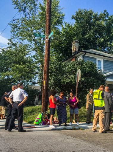 """Members of law enforcement, community leaders and family gather at the corner of Bernard and Cornelius for a vigil to honor Clarence """"Wade"""" Havvard Jr."""