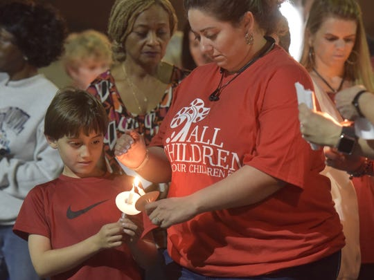 Christine Rials lights her son Isaiah's candle during a ceremony to honor the victims of last week's school shooting in south Florida. Vigils were held statewide on Feb. 19, 2018.