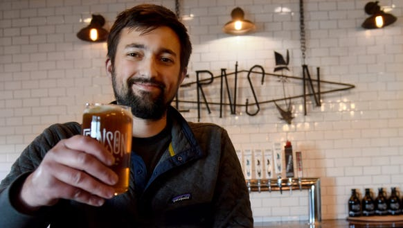 Blake Thompson holds their IPA in the taproom at Fernson