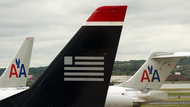 A US Airways jet and American Airlines planes are shown at Ronald Reagan Washington National Airport in Arlington, Va., in 2012.