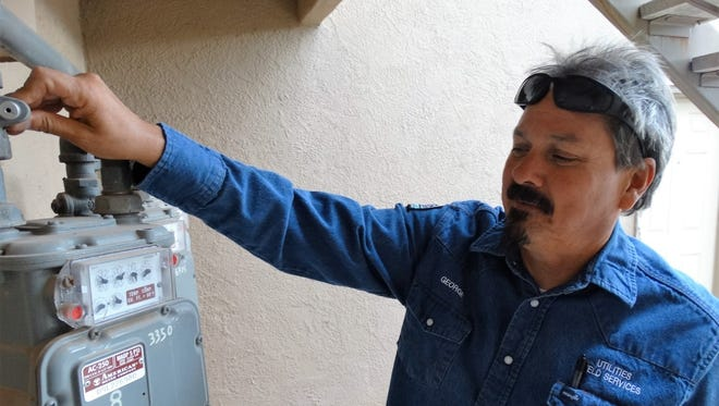 George Montoya, Las Cruces Utilities field service technician, installs a pinlock on a gas meter to deactivate gas service. New gas regulations require an adult over the age of 18 to be home during a gas activation.