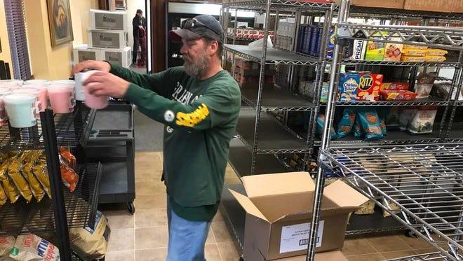 Dennis Clark, the floor manager of the Community Food Pantry of Merrill, stocks shelves on Oct. 31, 2017.