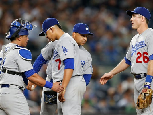 Los Angeles Dodgers catcher Carlos Ruiz, left, and manager Dave Roberts congratulate starting pitcher Julio Urias as he leaves the mound in the fourth inning of a baseball game against the New York Yankees in New York, Tuesday, Sept. 13, 2016. Second baseman Chase Utley joins the group on the mound. (AP Photo/Kathy Willens)