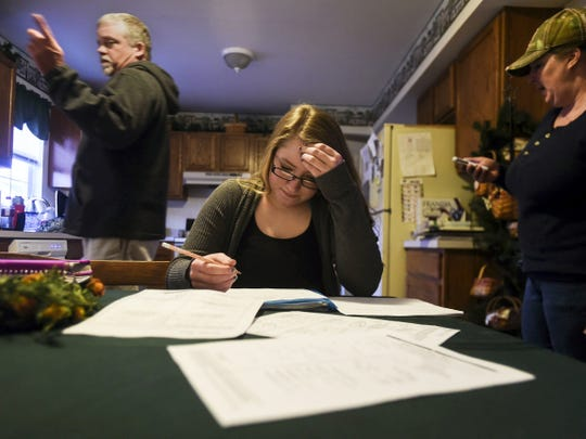 Kristin Reed, 15, works on her mathematics homework at the kitchen table March 24 at her home in Littlestown. Reed was once an honor roll student, now suffering from five concussions Reed struggles daily to maintain her grades in school. Her family, mother Stacy Reed, stepfather Kenneth Tull, and older brother Jeffrey Reed, frequently find time to help Kristin with her studies.