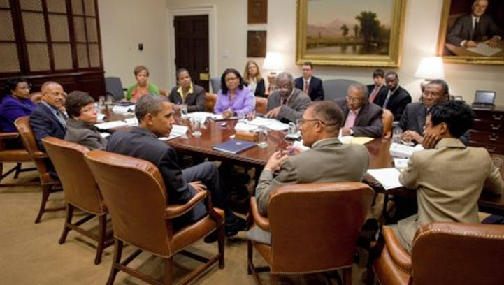 The writer, DeWayne Wickham, is seated immediately to the right of President Obama at a meeting in 2010.