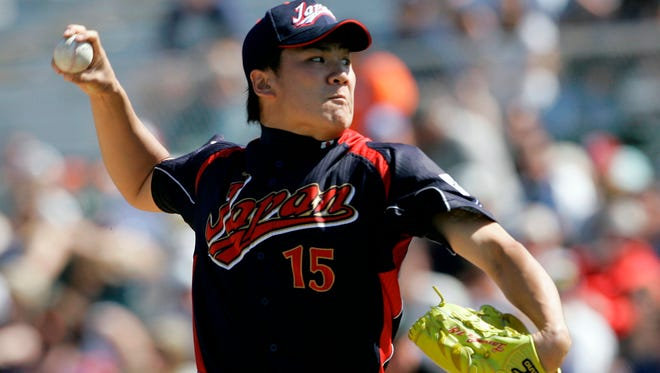 Japan's Masahiro Tanaka pitches to the San Francisco Giants during an exhibition game in 2009. The New York Yankees and Tanaka agreed on Wednesday to a $155 million, seven-year contract.
