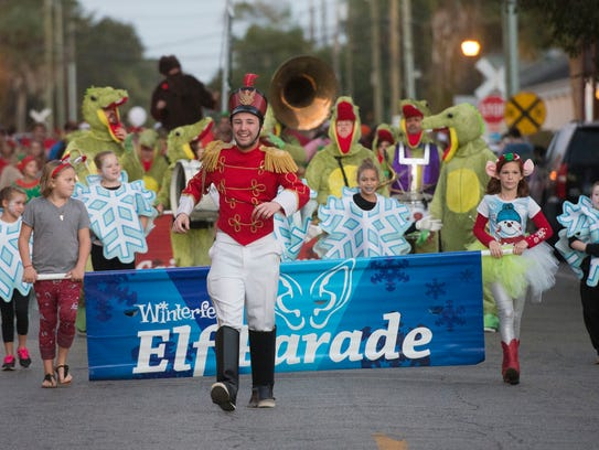 Ryan Ward, center, leads the annual Elf Parade through