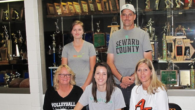 Brianna Bradford, center, signs a letter of intent to play volleyball for Seward County Community College on Monday at Lillywhite Gym in Aztec.