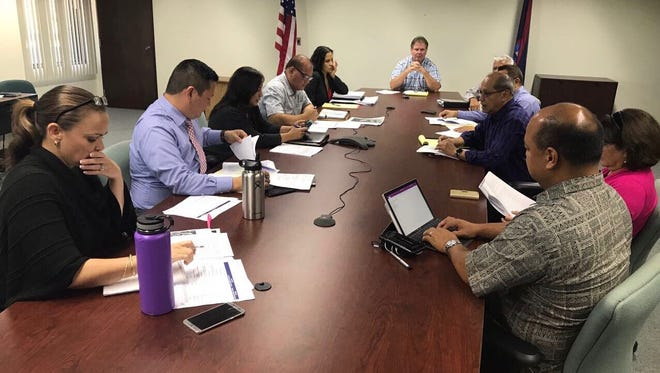 In this photo provided by the Government of Guam, government agency representatives on Monday, June 12, 2017, discuss a new law changing the procurement process for the rebuilding of Simon Sanchez High School.