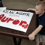 "In this July 19, 2013, photo, 4-year-old Jake Richards watches as his sister Stephanie makes signs reading ""Remember Aurora,"" during an event to mark the one-year anniversary of the Colorado movie theater shooting."