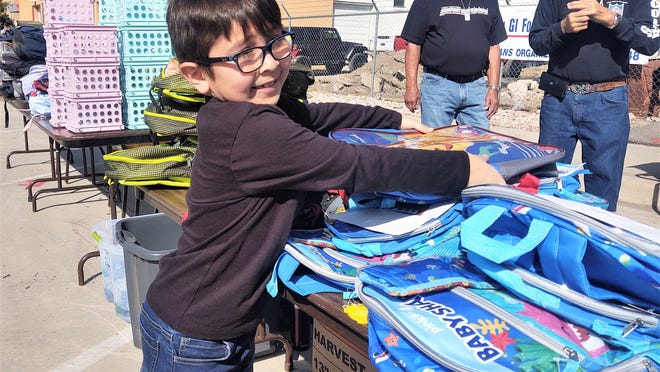 Visiting from Texas, Jax Lee, 6, prepares backpacks for distribution to schoolchildren during an American GI Forum giveaway.