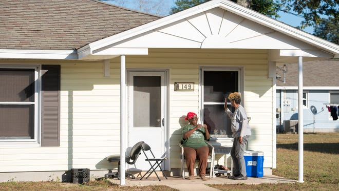 Moreno Court residents Willie Mae Rivers, left, and Pamela March have a laugh while talking on Rivers' front porch in Pensacola on Wednesday, December 7, 2016.