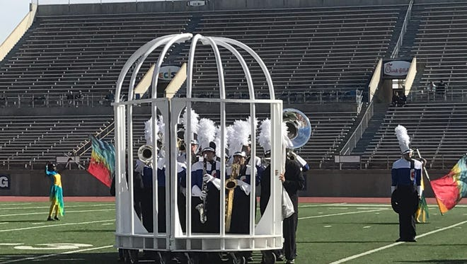 """The Cooper High School band completes its UIL marching performance with band members """"caged."""" The band advanced to the Area A finals Saturday in Odessa, vying in the evening for a state berth."""