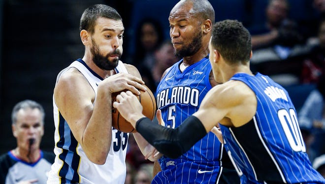 Memphis Grizzlies center Marc Gasol (left) drives the lane against Orlando Magic defenders Marreese Speights (middle) and Aaron Gordon (right) during fourth quarter action at the FedExForum in Memphis, Tenn., Wednesday, November 1, 2017.