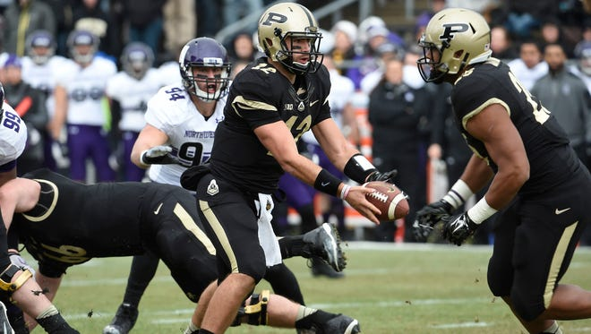 Purdue Boilermakers quarterback Austin Appleby (12) hands off to running back Brandon Cottom (25) in the first half against the Northwestern Wildcats at Ross Ade Stadium.