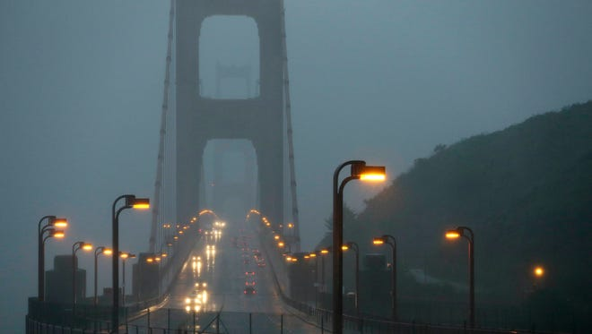Traffic moves slowly across the Golden Gate Bridge in the high winds and rain Dec. 11, 2014, in this view from Sausalito, Calif.