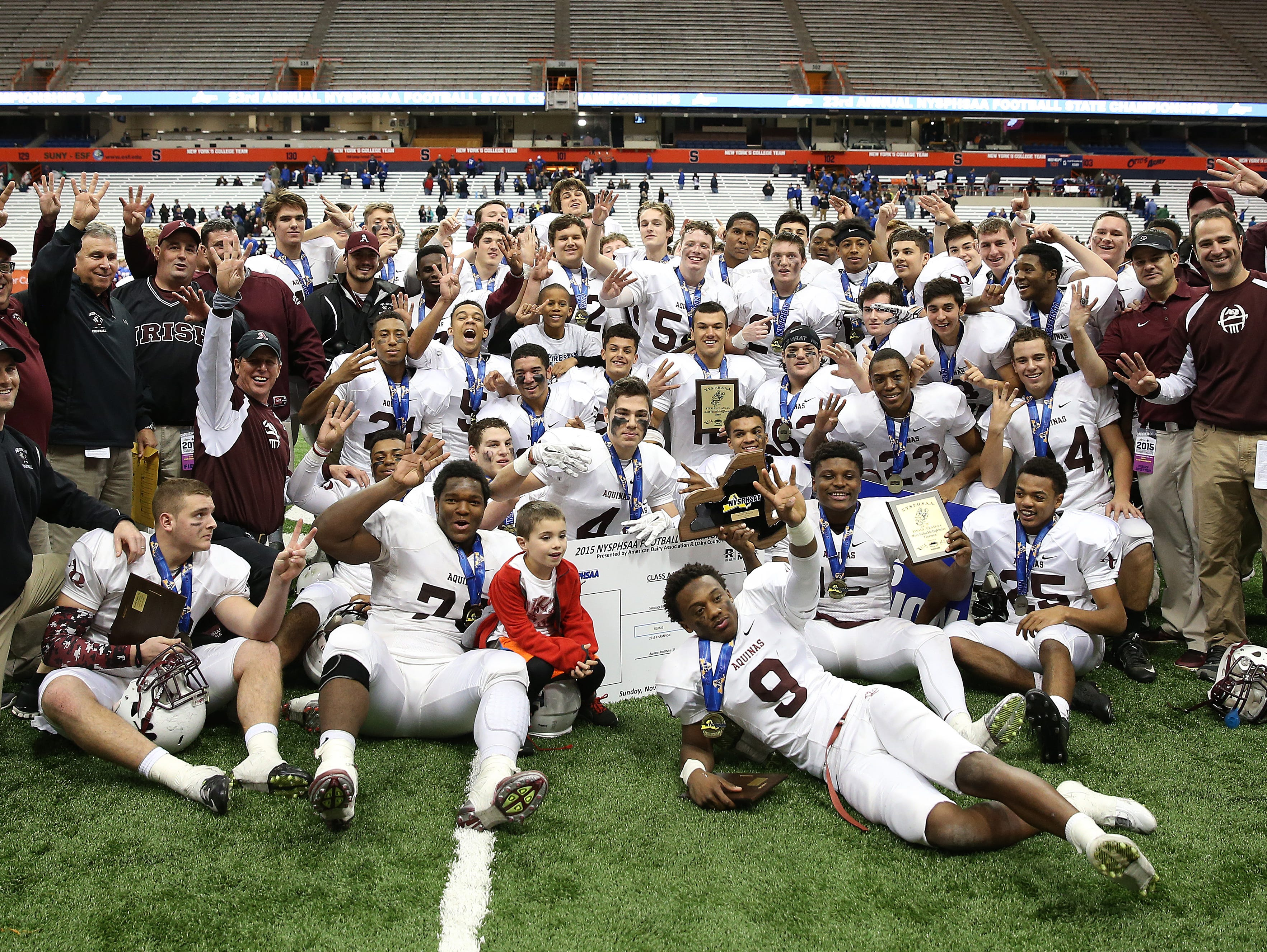 Aquinas players gather for a team photo after beating Saratoga Springs 44-19 to win the State Class AA title.
