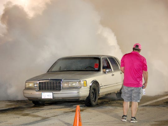 VERNON – Montana Wells draws cheers from the crowd as the spinning tires of his 1992 Lincoln Town Car fills the air with clouds of smoke at the annual Summer's Last Blast Burn Out Friday evening in Vernon. The popular event was sponsored the members of the Vernon Street Machine and Classics Association.
