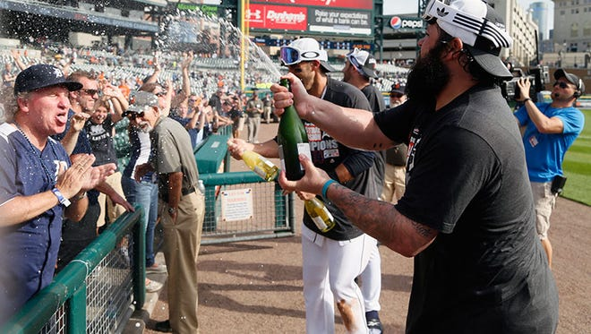 Tigers pitcher Joba Chamberlain helps fans celebrate the AL Central Division title on Sunday at Comerica Park.