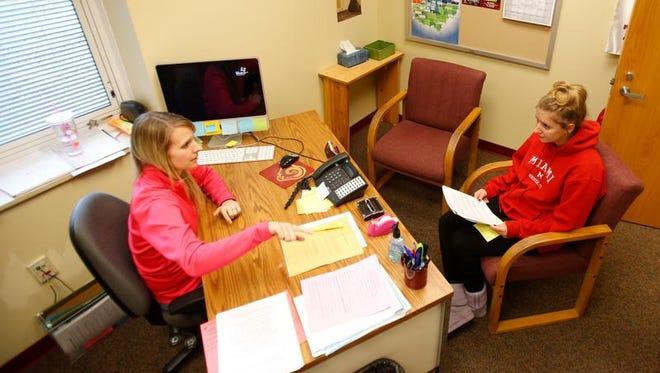 Ross High School counselor Rachel Lieberth, left, talks about scholarship opportunities with senior Haley Baker. Baker will be attending Wright State University.