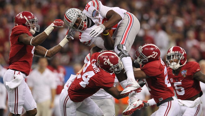 Ohio State Buckeyes quarterback Cardale Jones attempts to leap over Alabama Crimson Tide defensive backs Geno Smith, Nick Perry and Eddie Jackson in the first quarter of the 2015 Sugar Bowl at Mercedes-Benz Superdome.