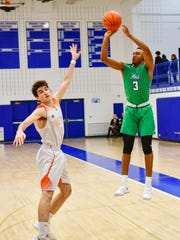 Novi's Jiovanni Miles (3) launches a jump shot over