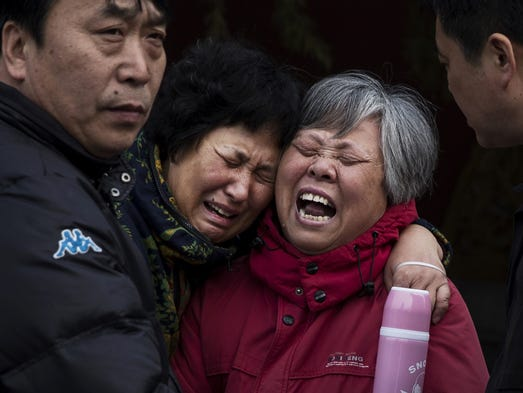 Chinese relatives of a passenger on flight MH370 weep