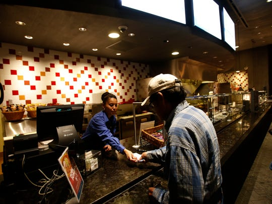 Hostess and cashier Calandra Begay serves a customer on Wednesday at Northern Edge Navajo Casino in Fruitland.