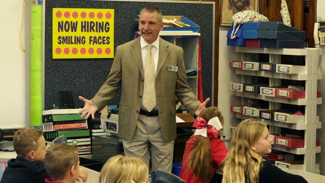 John Dinegan, Lourdes Academy System president, greets students Tuesday at Lourdes Academy Elementary School in Oshkosh.