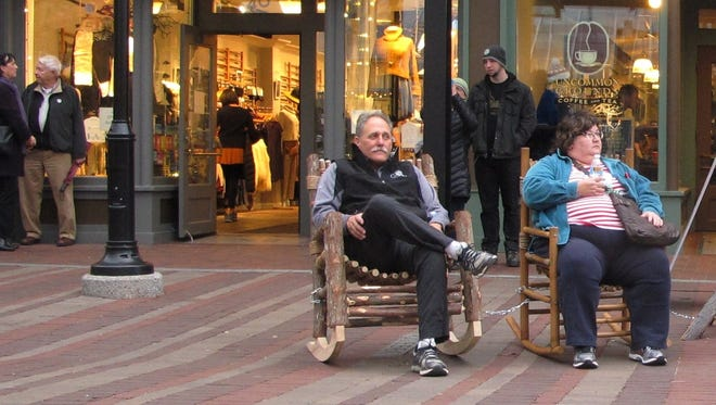 Doug Best, center, of Martha's Vineyard and Chris van Jelgerhuis of Clearwater, Florida, relax late Friday afternoon on Church Street in Burlington. Some businesses, including Sweet Lady Jane, left their doors open during the balmy spell.