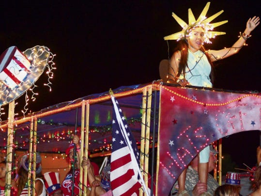 Taking a victory lap, Hernandez Plumbing celebrates their win for best float at the 2014 Las Cruces Electric Light Parade. Today's parade follows the Electic 5K and 1 Mile Fun Run race and the monthly Downtown Ramble on Main Street.